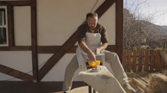 Potter sculpt at wheel machine in gray clay. Man in white apron work outside at - stock footage