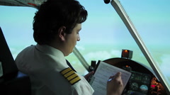 Serious aircrew commander filling in flight papers, autopilot steering plane Stock Footage