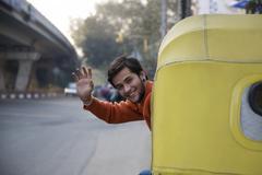 Man waving from an auto rickshaw Stock Photos
