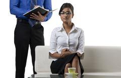 Businesswoman giving brief to an executive Stock Photos