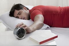 Man switching off his alarm clock Stock Photos