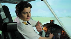 Serious pilot making thumbs up gesture at camera, recommending reliable airline Stock Footage