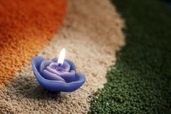 A candle in the middle of coloured pulses Stock Photos