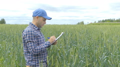 Farmer in a plaid shirt controlled his field and writing notes - stock footage