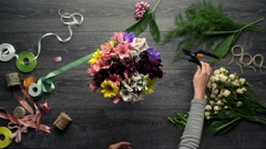 Girl's hands making bouquet of flowers over wood background. From above. Top Stock Footage