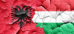 Albania flag with Hungary flag on a grunge cracked wall - stock illustration