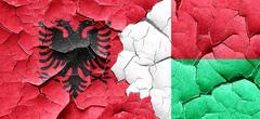 Albania flag with Madagascar flag on a grunge cracked wall - stock illustration