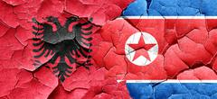 Albania flag with North Korea flag on a grunge cracked wall - stock illustration