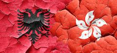 Albania flag with Hong Kong flag on a grunge cracked wall - stock illustration