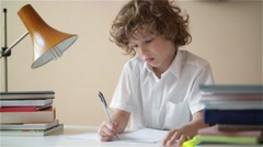 Cute Boy doing homework. Child education, student writes in a notebook Stock Footage