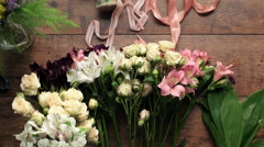 Girl's hands making bouquet of flowers over wood background. From above. Top - stock footage