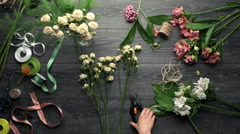 Girl's hands making bouquet of flowers over wood background. Slow motion. From Stock Footage