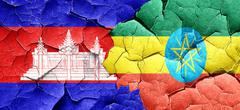 Cambodia flag with Ethiopia flag on a grunge cracked wall Stock Illustration