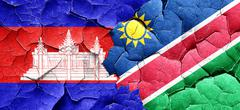 Cambodia flag with Namibia flag on a grunge cracked wall - stock illustration