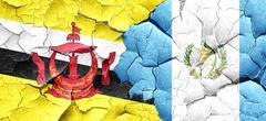 Brunei flag with Guatemala flag on a grunge cracked wall - stock illustration