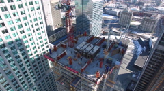 Building under construction surounded by skyscrapers - stock footage