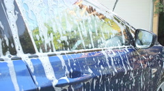 white foam flows down on glass and blue car body. Car wash machine. - stock footage