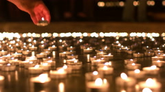 Woman Placing Her Candle in Between Other Candles - stock footage