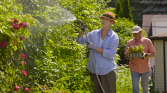 Senior couple ready to plant flowers in their garden - stock footage