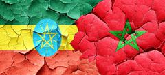 Ethiopia flag with Morocco flag on a grunge cracked wall - stock illustration