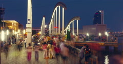 Bridge over Port Vell marina. Tourists walking on Rambla del Mar at night Stock Footage