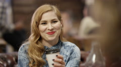 4K Portrait smiling hipster girl drinking coffee in city coffee shop Stock Footage