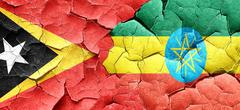 east timor flag with Ethiopia flag on a grunge cracked wall - stock illustration