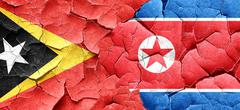 east timor flag with North Korea flag on a grunge cracked wall - stock illustration