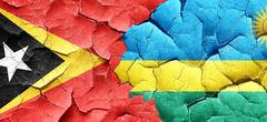 east timor flag with rwanda flag on a grunge cracked wall - stock illustration