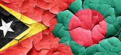 east timor flag with Bangladesh flag on a grunge cracked wall - stock illustration