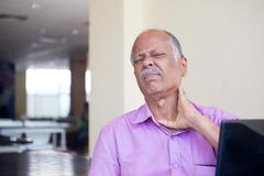 Closeup portrait, elderly gentleman in pink shirt with cramping neck pain aft Stock Photos