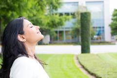 Closeup portrait, young woman in white shirt breathing in fresh crisp air aft Stock Photos