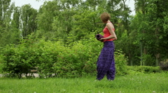 The young blonde girl practicing yoga in the park. The girl unrolling a mat. - stock footage