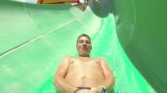 Man having fun sliding down a waterslide in public swimming pool Stock Footage