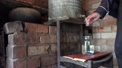 Villager man hands fill glass with home made illegal alcohol. 4K Stock Footage