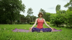 The young blonde girl practicing yoga in the park. The Lotus posture. Meditation - stock footage