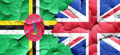 Dominica flag with Great Britain flag on a grunge cracked wall - stock illustration