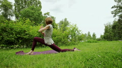 The young blonde girl practicing yoga in the park. Asanas the salutation of sun Stock Footage