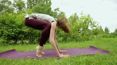 The young blonde girl practicing yoga in the park. Asana on the balance - stock footage