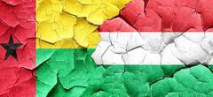 Guinea bissau flag with Hungary flag on a grunge cracked wall Stock Illustration