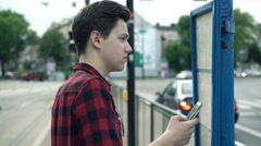 Young teenager checking departure timetable board at tram stop Stock Footage