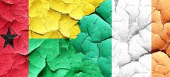 Guinea bissau flag with Ireland flag on a grunge cracked wall - stock illustration