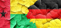 Guinea bissau flag with Germany flag on a grunge cracked wall - stock illustration