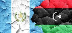 guatemala flag with Libya flag on a grunge cracked wall - stock illustration