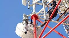 Workers working on the installation of telecommunication antennas climb to great - stock footage