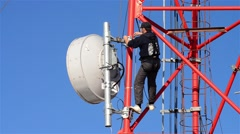 Workers working on the installation of telecommunication antennas climb to great Stock Footage