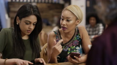 4K Happy young friends in city coffee shop chatting & using technology Stock Footage