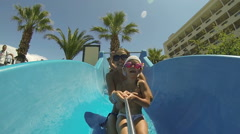 Child with mother on water slide at aquapark. Summer holiday Stock Footage