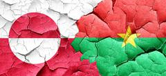 Greenland flag with Burkina Faso flag on a grunge cracked wall Stock Illustration