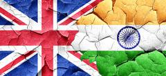 Great britain flag with India flag on a grunge cracked wall - stock illustration